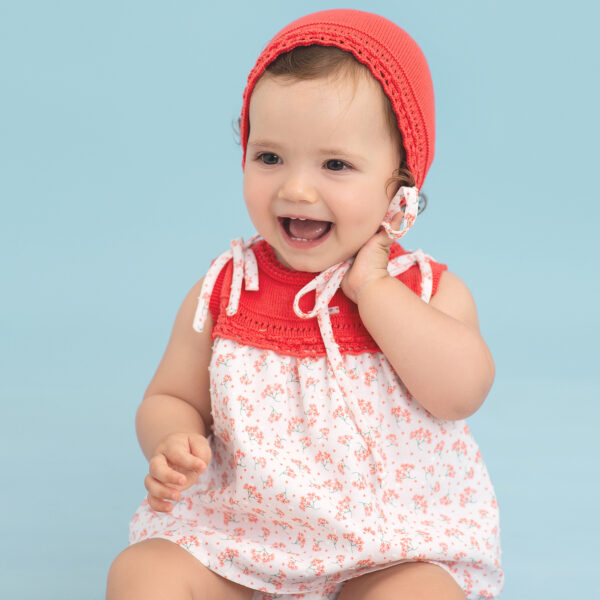Foque Floral Baby Dress Set. Orange and white dress set for baby girls by Foque, made in soft, lightweight cotton, with a pretty orange and green floral print. The dress has a knitted bodice with bow trims, a cross-over button fastening back and lightweight lining. There are matching knickers and an orange cotton knit bonnet that fastens with ties under the chin.