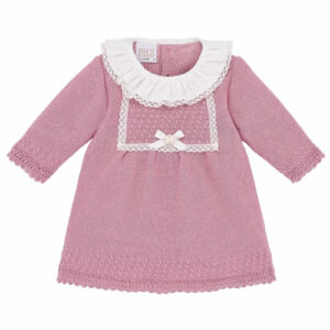 """Paz Rodriguez """"Nostalgia"""" Dress. Dusky pink dress for baby girls by Paz Rodriguez. Luxuriously soft, it is made with a cashmere and cotton blend knit. It has an ivory, lace-trimmed ruffle collar, white bow on the front, and ivory scalloped trims. Fastening with buttons on the back, it has a small pearlized logo tag."""