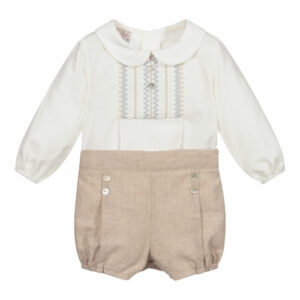 """Paz Rodriguez Beige Set """"Baul"""". Baby boys ivory shirt and beige shorts set by Paz Rodriguez. The lightweight cotton twill shirt has lovely smocking detail with blue and beige embroidery and decorative mother-of-pearl buttons. The lined, cotton-blend shorts have pleats and decorative buttons on the front, and an adjustable waistband."""