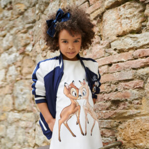 Monnalisa Kids Disney Bambi Dress. Dress by Monnalisa, with a beautiful beige Disney© Bambi print on the front. It is made in silky smooth fabric with a slight stretch and sweet puffed sleeves. The removable soft faux fur collar fastens with a button and has a pretty ivory bow on the side.